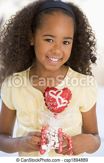 Young girl on Valentine\\\'s Day holding love themed balloon smilin - csp1894889
