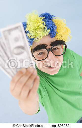 Young boy wearing clown wig and fake nose holding money - csp1895082