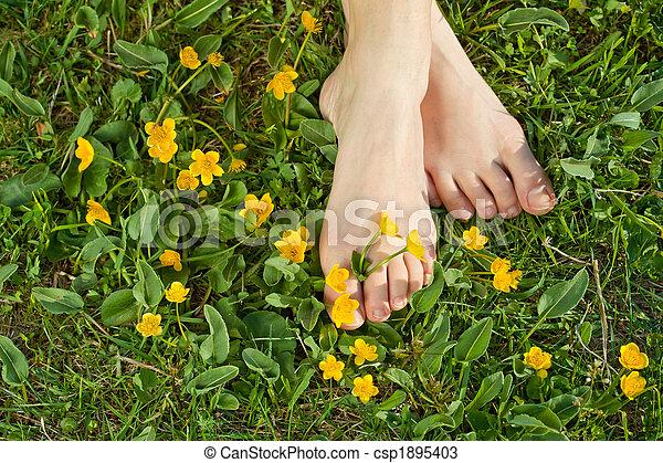 Woman resting her feet in the fresh spring vegetation - csp1895403