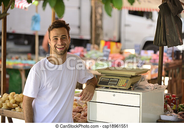 Small business owner selling organic fruits and vegetables at an open street market. - csp18961551