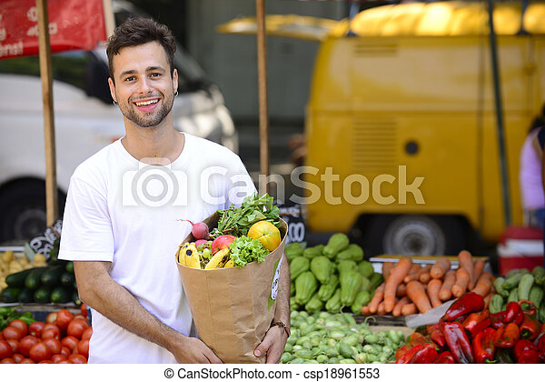 Man carrying a shopping paper bag full of fruits and vegetables at an open street market. - csp18961553