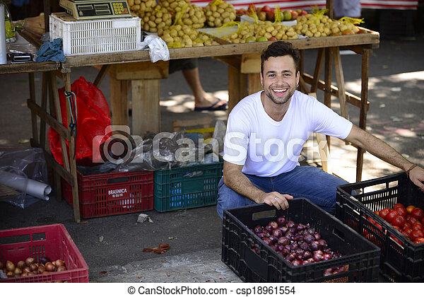 Small business owner selling organic fruits and vegetables at an open street market. - csp18961554