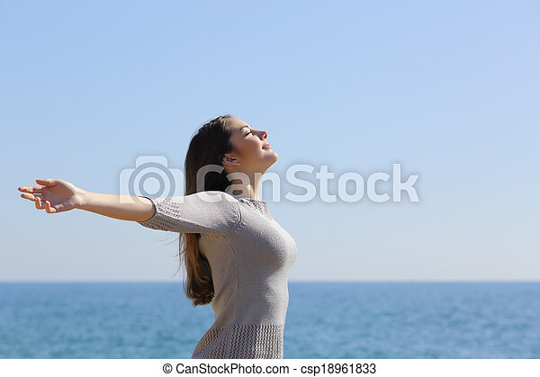 Happy woman breathing deep fresh air and raising arms on the beach - csp18961833