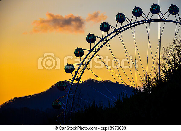 Silhouette of a ferris wheel at sunset - csp18973633