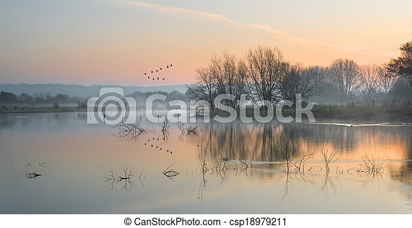 Landscape of lake in mist with sun glow at sunrise - csp18979211