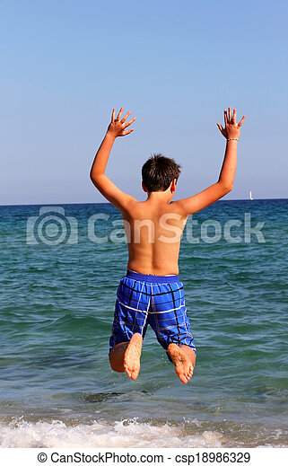 Boy jumping on the sea beach on summer holidays - csp18986329