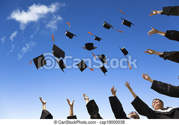 Students throwing graduation hats in the air celebrating - csp19000038