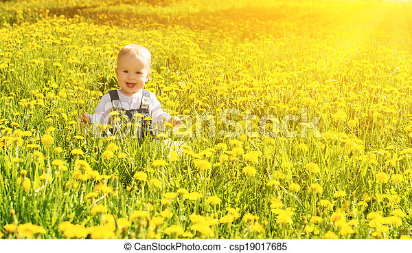 Beautiful happy little baby girl sitting on a green meadow with yellow flowers dandelions on the nature in the park - csp19017685