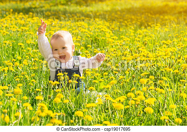 Beautiful happy little baby girl sitting on a green meadow with yellow flowers dandelions on the nature in the park - csp19017695
