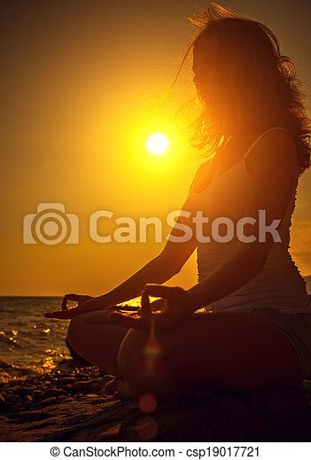 woman meditating in lotus pose on the beach at sunset - csp19017721