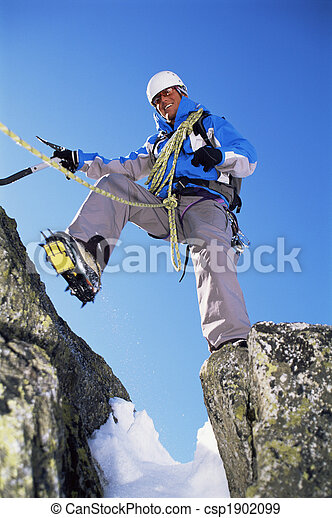 Young man mountain climbing on snowy peak - csp1902099