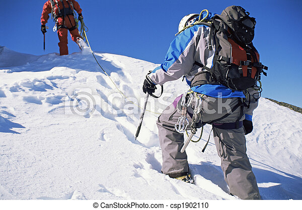Young men mountain climbing on snowy peak - csp1902110