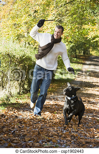 Man exercising dog in woodland - csp1902443