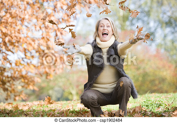 Senior woman throwing leaves in the air - csp1902484