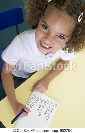 Girl learning to write name in primary class - csp1902784