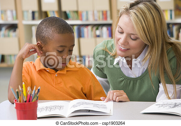 Kindergarten teacher helping student with reading skills - csp1903264
