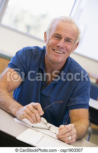 Mature male student holding glasses in class - csp1903307