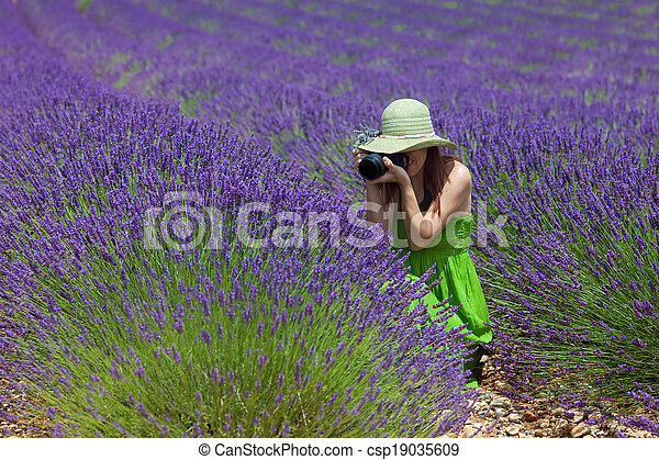 Beautiful woman among lavender photographing some lavender flowers. Wearing green dress and hat, decorated with lavender twigs. Placed in foreground, side view. - csp19035609