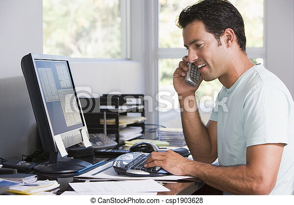 Man in home office on telephone using computer and smiling - csp1903628