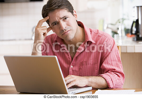 Man in kitchen using laptop frowning - csp1903655