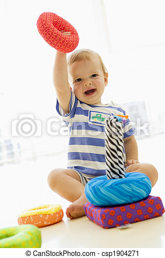 Baby indoors playing with soft toy - csp1904271