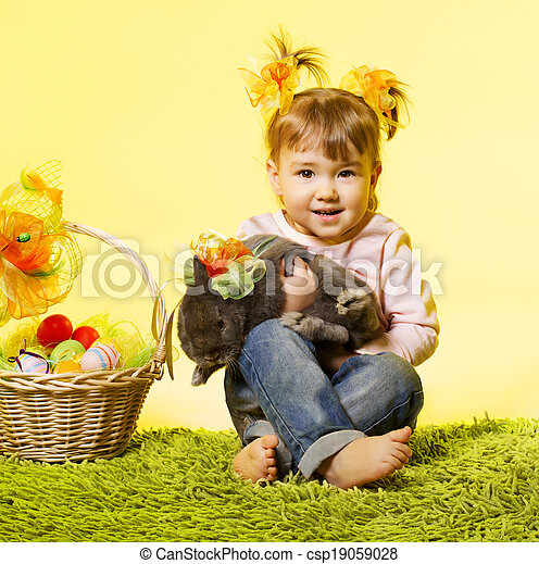 Easter little girl, kid holding bunny rabbit basket eggs over yellow background - csp19059028