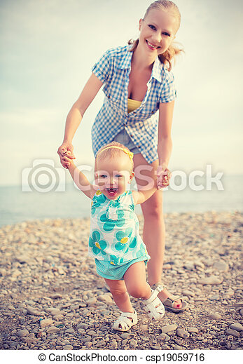 happy family on nature mother and baby doing first steps - csp19059716