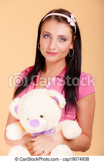Childish young woman infantile girl in pink hugging teddy bear toy - csp19074938
