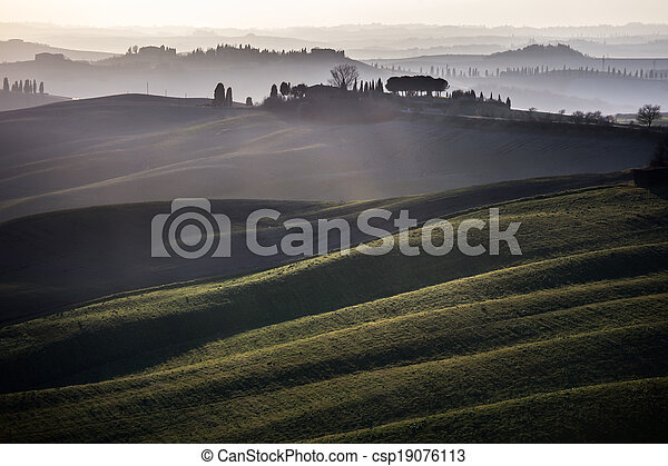 Tuscany, rolling hills on sunset. Crete Senesi rural landscape and sunlight. Green fields, a farm with trees. Siena, Italy - csp19076113