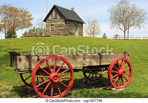 Pioneer log cabin and wooden wagon - csp1907796