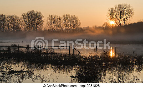Landscape of lake in mist with sun glow at sunrise - csp19081828