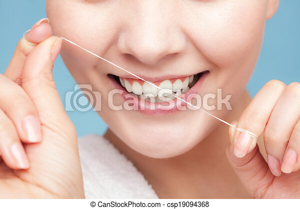 Girl cleaning teeth with dental floss. Health care - csp19094368