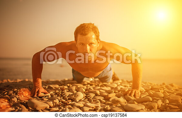 man athlete trains, practicing, playing sports pushed on the nature on the beach - csp19137584