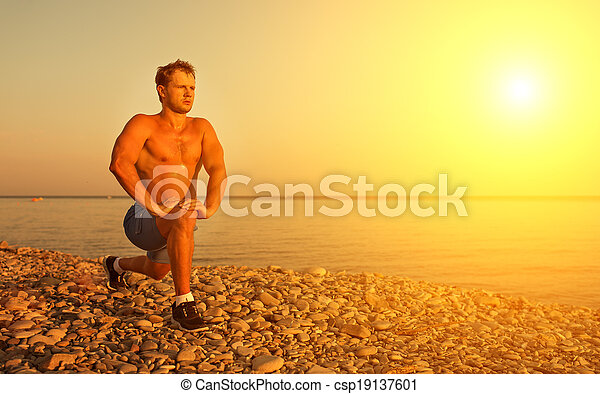 man athlete practicing, playing sports and yoga on the beach at sunset - csp19137601