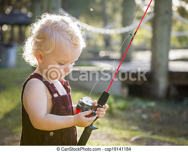 Cute Young Boy With Fishing Pole at The Lake - csp19141184