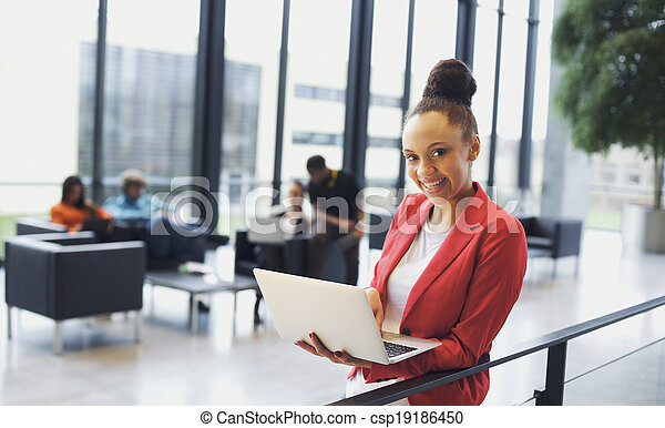 Beautiful young african woman with laptop in modern office - csp19186450