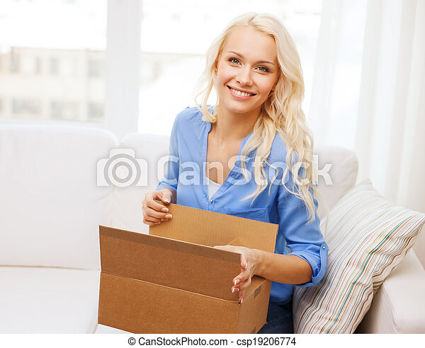smiling young woman opening cardboard box at home - csp19206774
