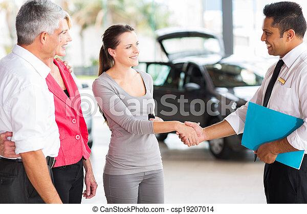 vehicle salesman handshake with young adult customer - csp19207014