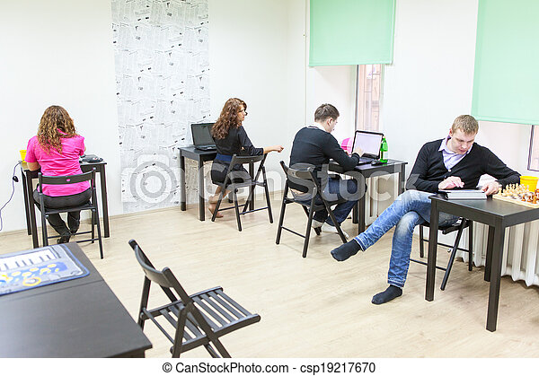 Young adults surfing internet in co-working room - csp19217670