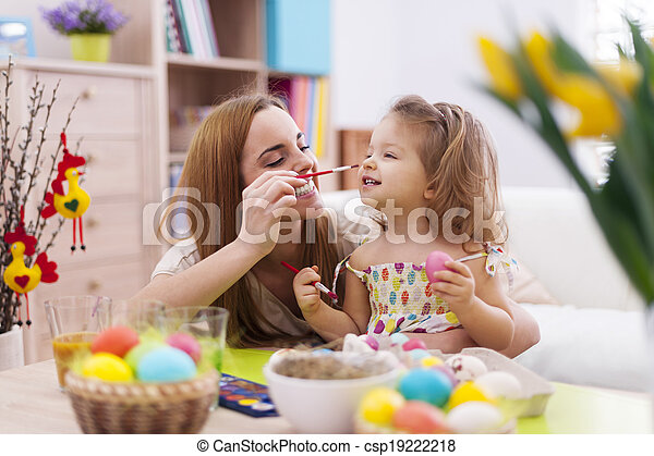 Mother and her baby have fun while painting easter eggs - csp19222218
