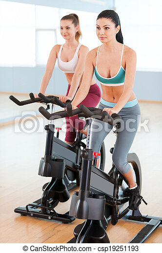 Women on exercise bikes. Two beautiful young women in sports clothing exercising on gym bicycles - csp19251193