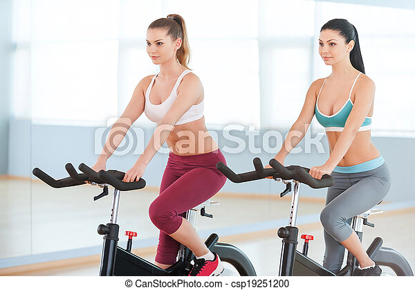 Cycling on exercise bikes. Two attractive young women in sports clothing exercising on gym bicycles - csp19251200