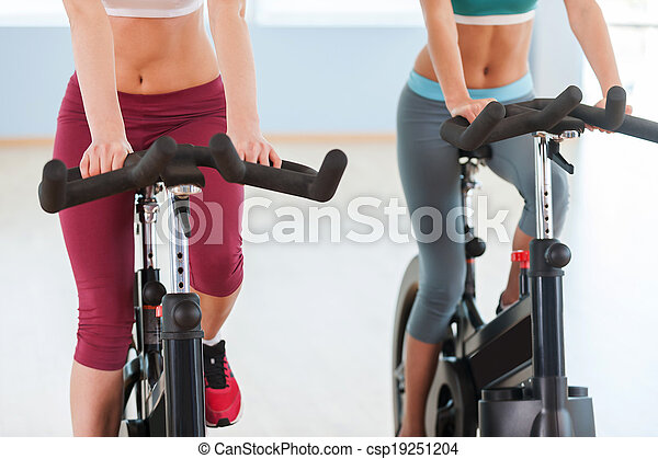 Girls on exercise bikes. Cropped image of two young women in sports clothing exercising on gym bicycles - csp19251204
