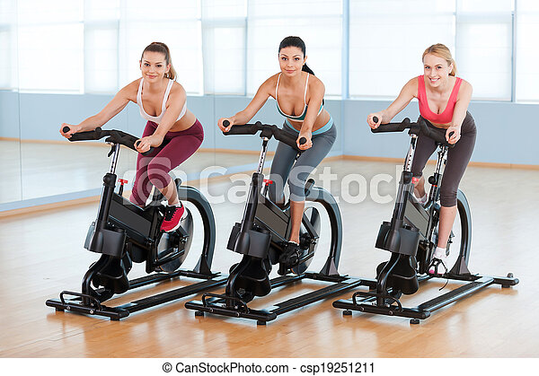 Cycling on exercise bikes. Two attractive young women in sports clothing exercising on gym bicycles - csp19251211