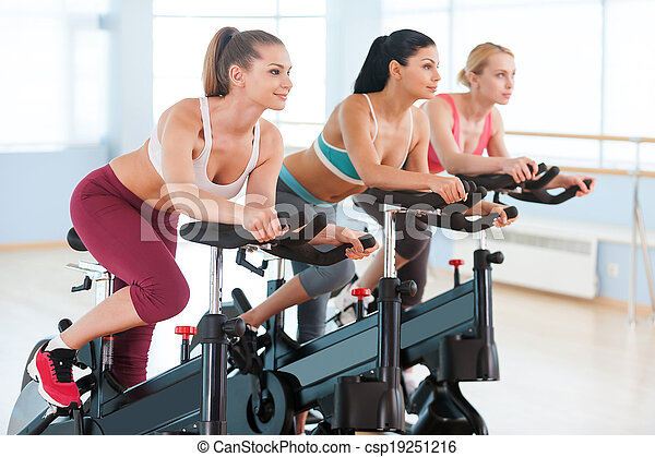 Cycling on exercise bikes. Two attractive young women in sports clothing exercising on gym bicycles - csp19251216