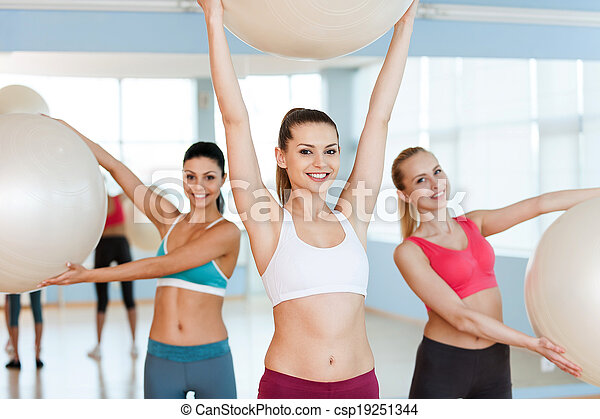 Women with fitness balls. Three beautiful young women in sports clothing exercising with fitness balls and smiling at camera - csp19251344
