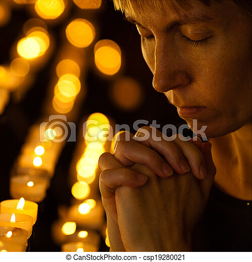 Prayer praying in Catholic church near candles. Religion concept. - csp19280021