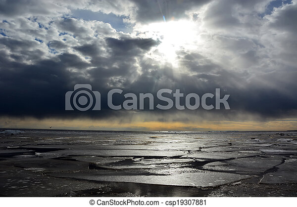 Sun through the stormy clouds at the frozen sea - csp19307881