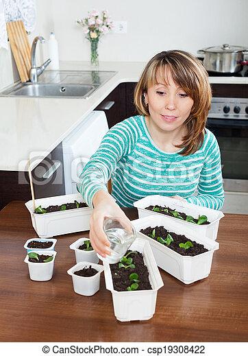 woman in green watering seedlings