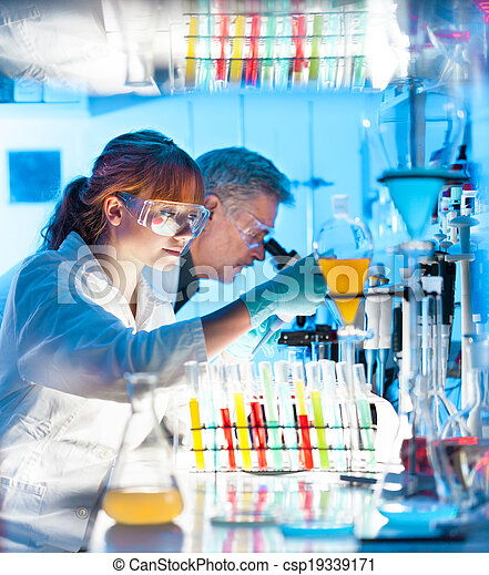 Attractive young female scientist and her senior male supervisor looking at the cell colony grown in the petri dish in the life science research laboratory (biochemistry, genetics, forensics, microbiology..)